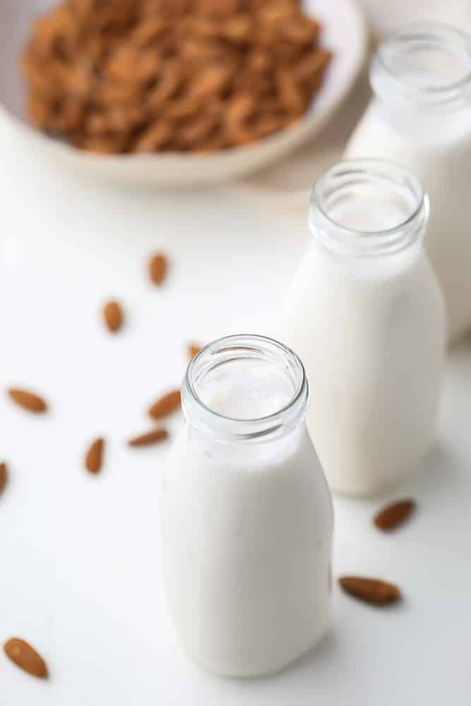 two glass milk bottles holding white almond milk, almonds in background