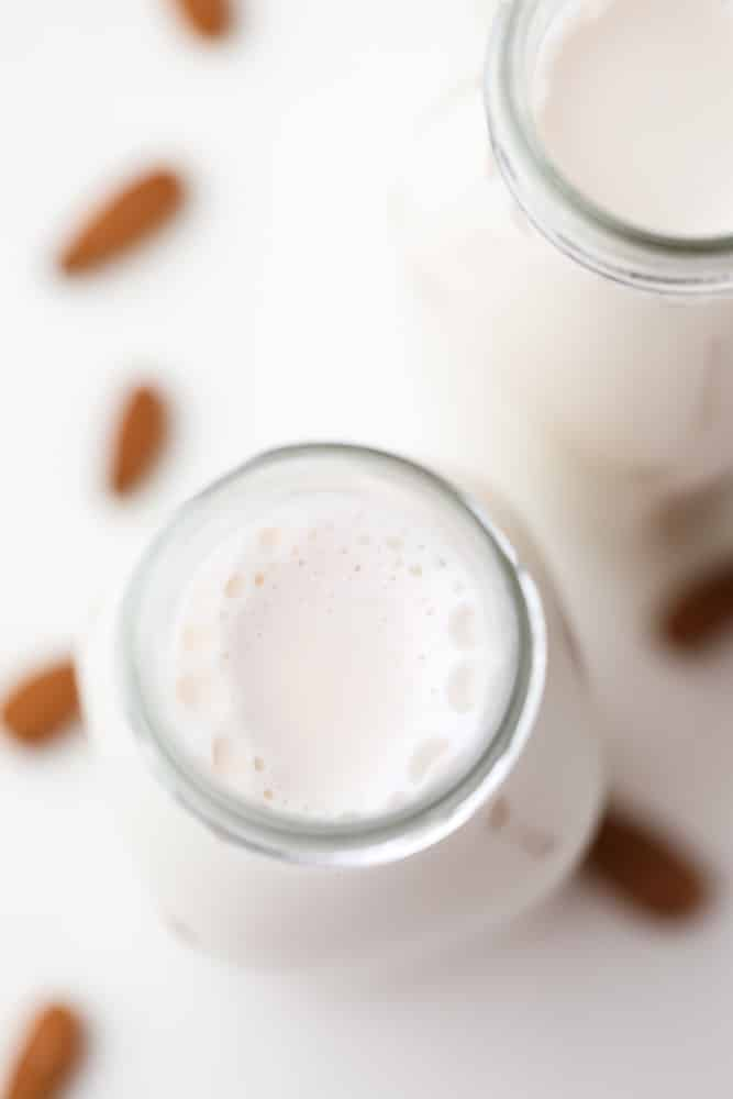 looking down on a bottle with white milk, almonds in background