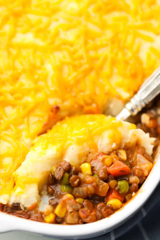 casserole dish with lentil shepherd's pie and a spoon serving it