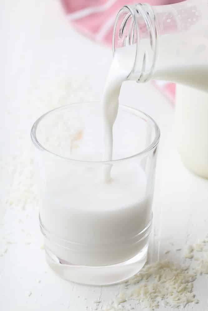 cup of milk being poured from a milk jug with coconut around it