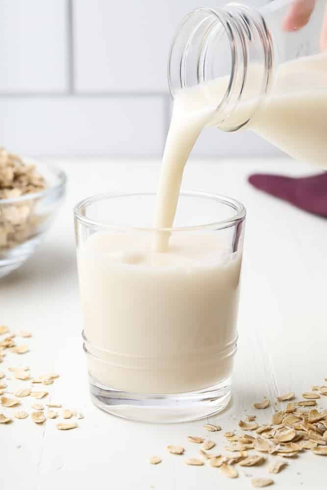 oat milk being poured into a glass