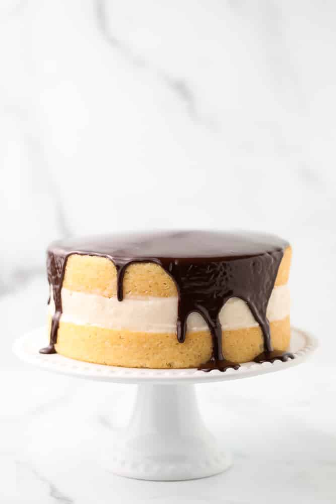 marble backdrop of cake with ganache and cream filling