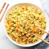 square image of a bowl of rice with veggies in it and chopsticks