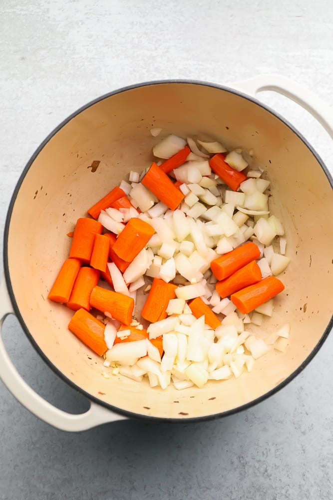 Large pot with raw onions and carrots