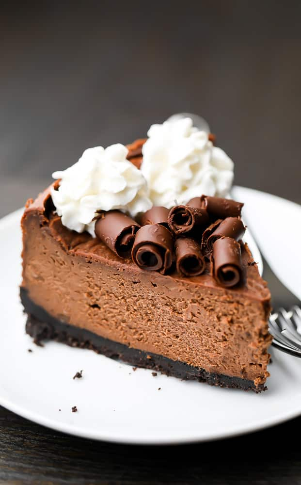 Slice of vegan chocolate cheesecake with whipped cream and chocolate on top on a white plate
