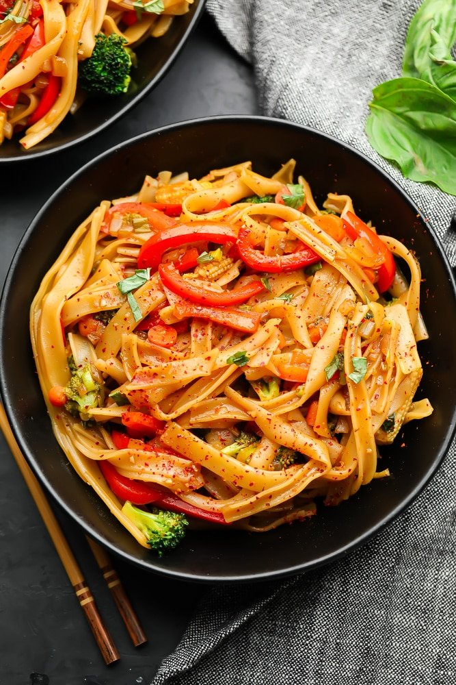 two bowls of noodles and veggies