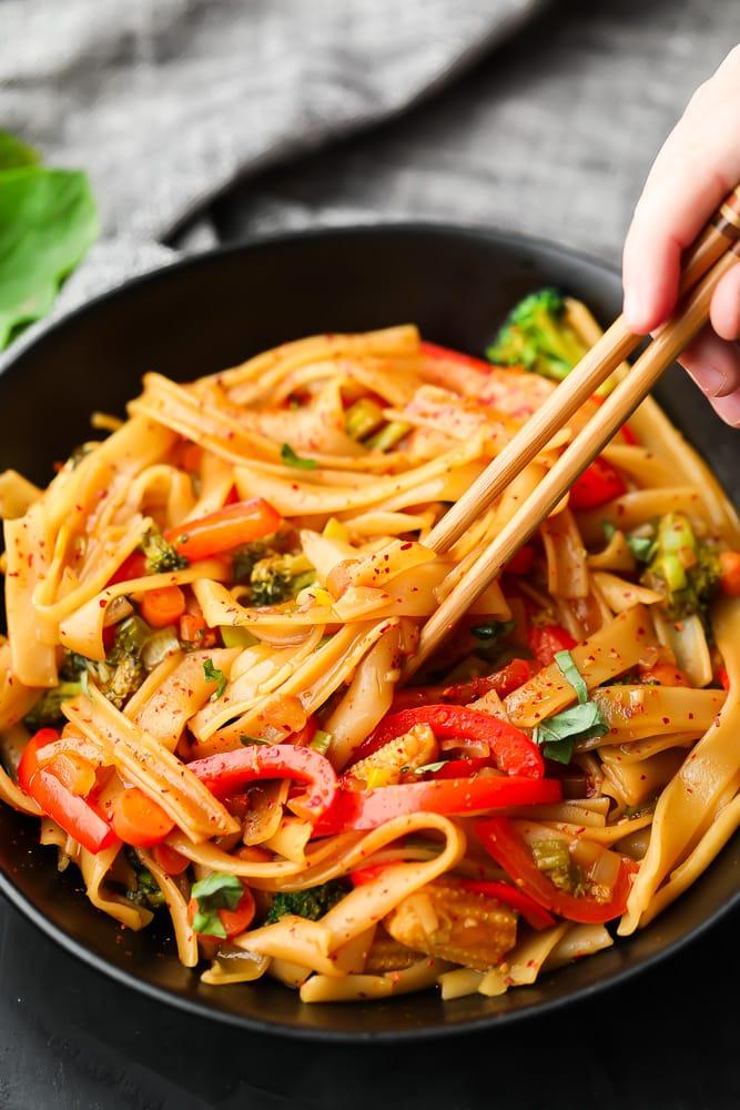chopsticks holding some noodles out of black bowl