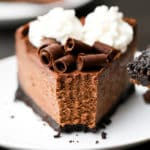 Close up of a slice of chocolate cheesecake on a white plate with a bite taken out of it