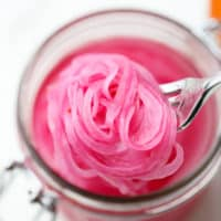 close up of a fork taking a scoop of pickled red onions out of a mason jar