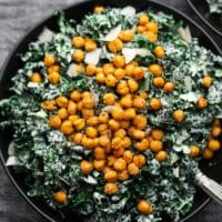 close up of kale caesar salad in a black bowl with chickpea croutons