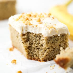 square image of a piece of cake with frosting and walnuts on top