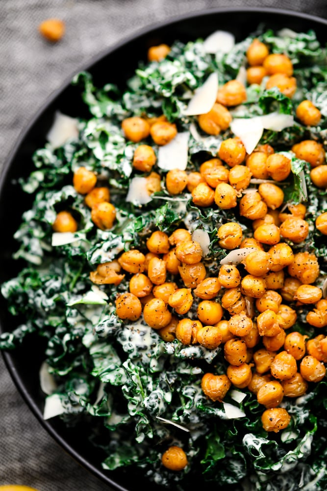 close up of kale caesar salad in a black bowl topped with chickpea croutons