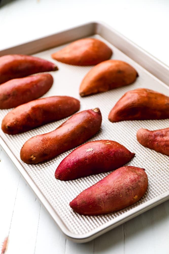 halved sweet potatoes on a baking sheet
