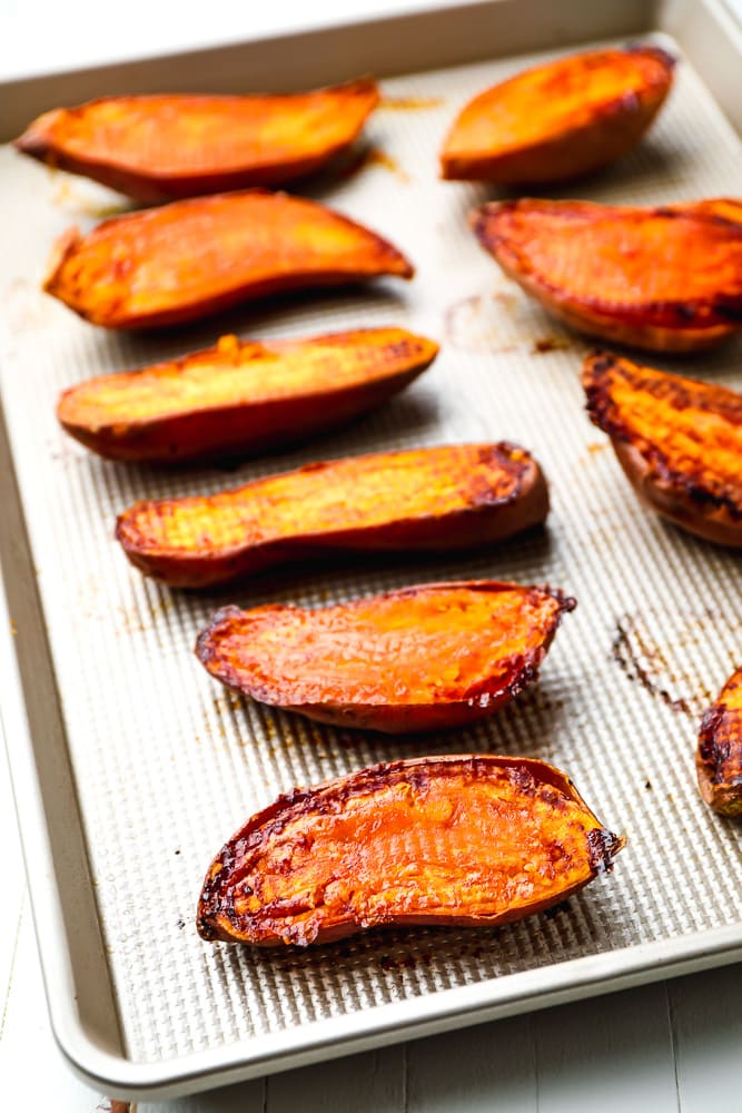 baked sweet potatoes flesh side up on a baking sheet