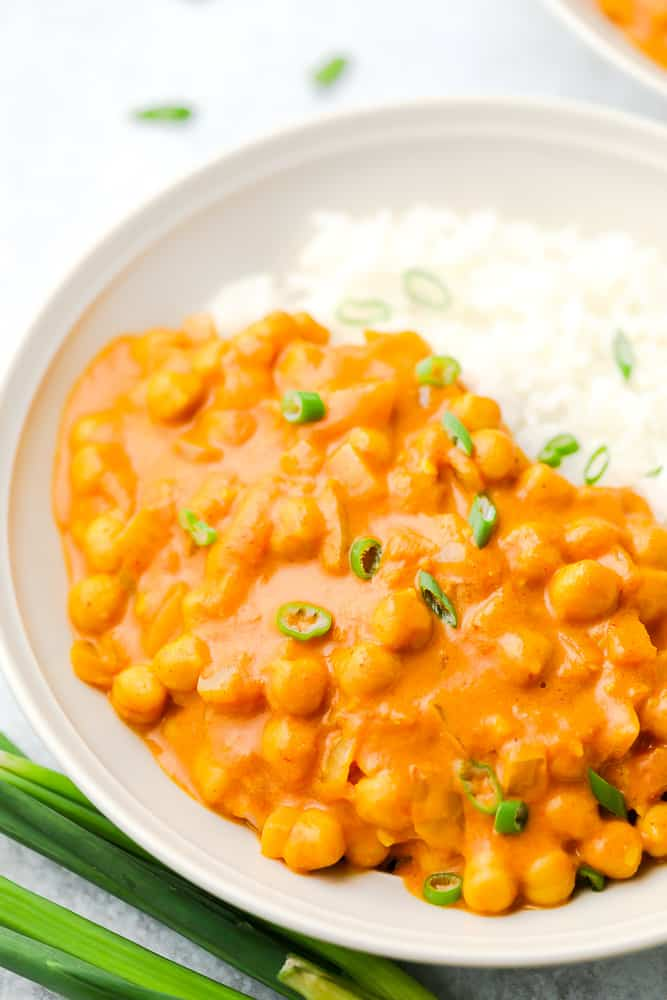 close up up bowl with beans in orange curry sauce and rice