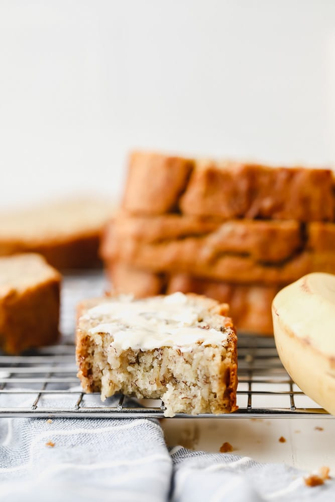buttered and bitten slice of banana bread on a cooling rack
