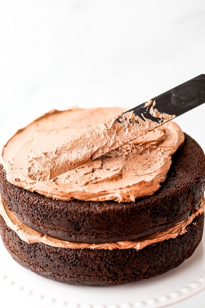 frosting a chocolate cake with chocolate frosting