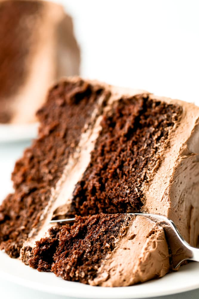 close up of a fork taking a bite out of a piece of chocolate cake