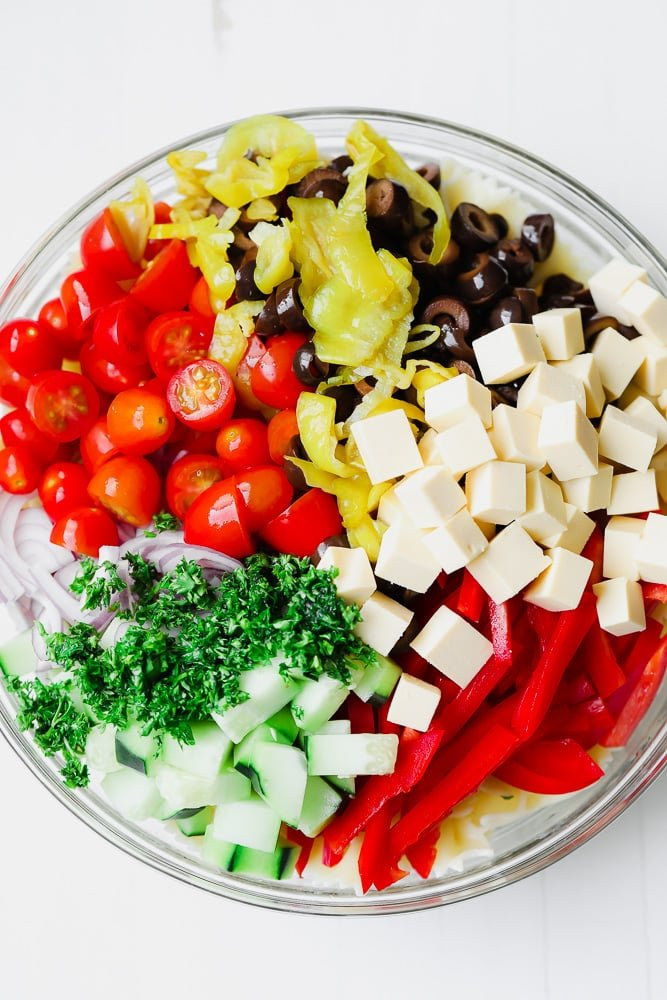 chopped veggies and vegan cheese in a glass bowl
