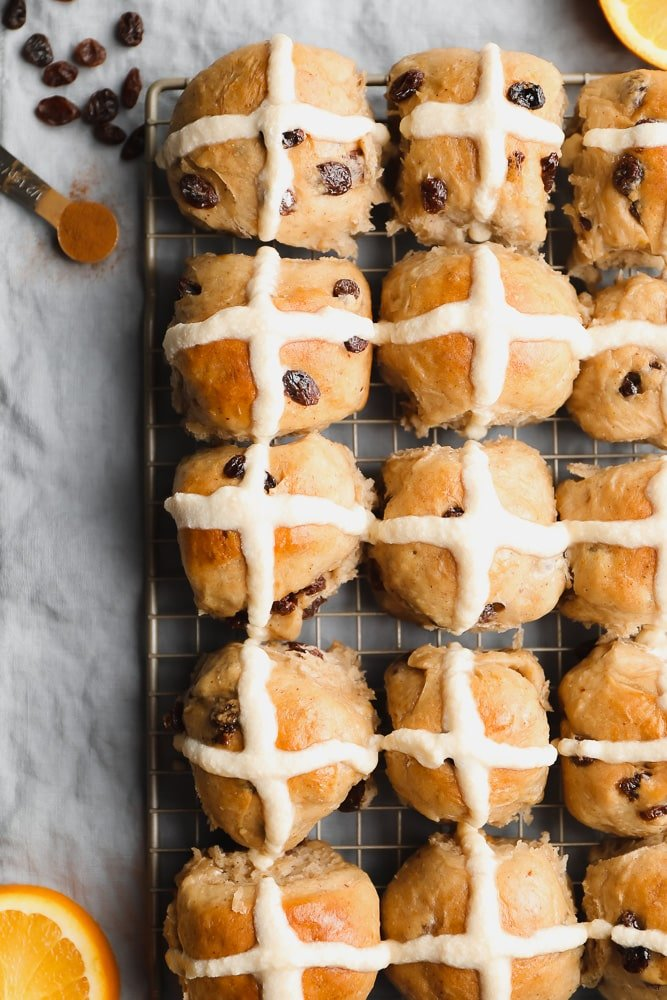 many rolls with cross icing on a cooling rack