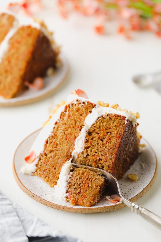 two pieces of cake on plates, carrot with white frosting