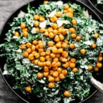 close up of green caesar salad in a black bowl with chickpea croutons