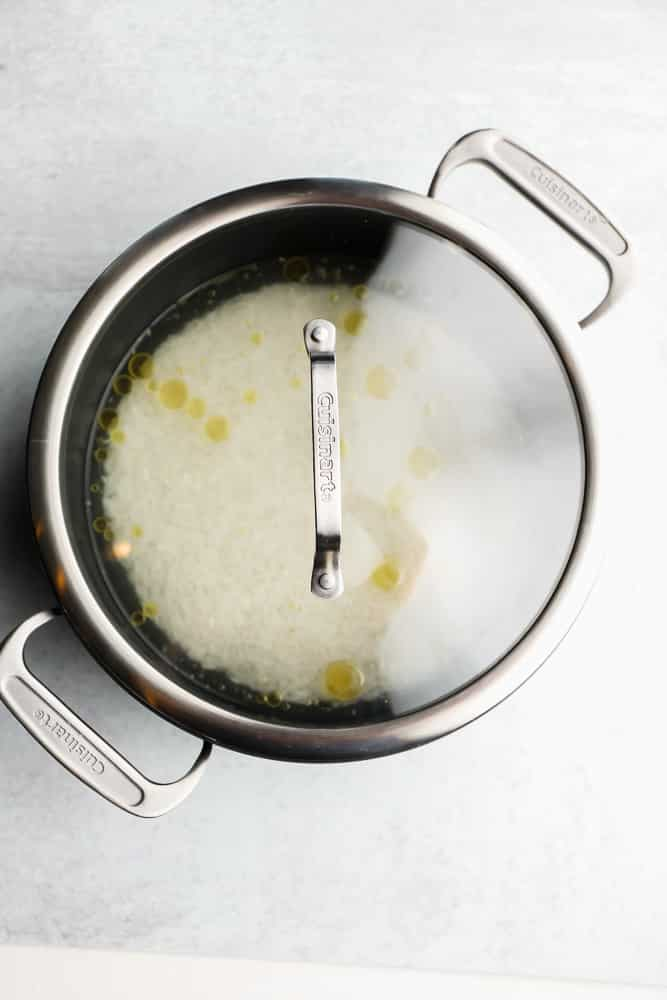 white rice, oil, and water in a black pot with a glass lid on top