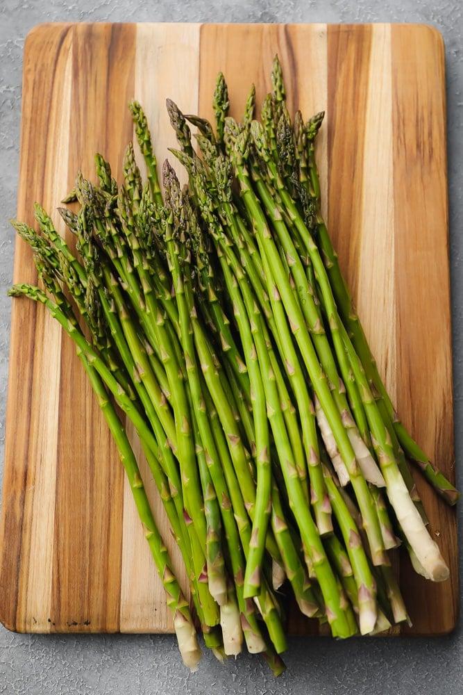 raw asparagus on a wood board