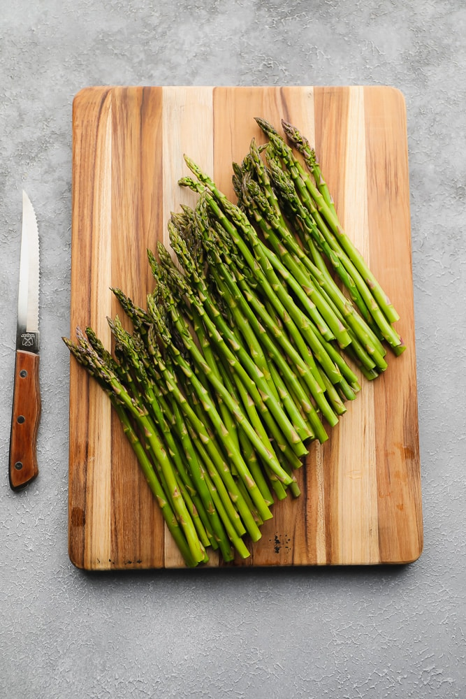 raw asparagus on a wood board next to a knife