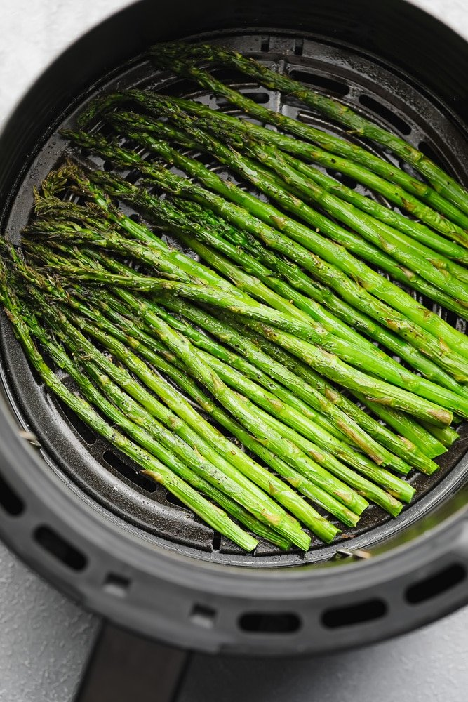 cooked asparagus in an air fryer basket
