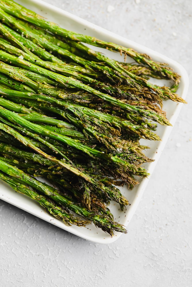 cooked asparagus on a white serving plate