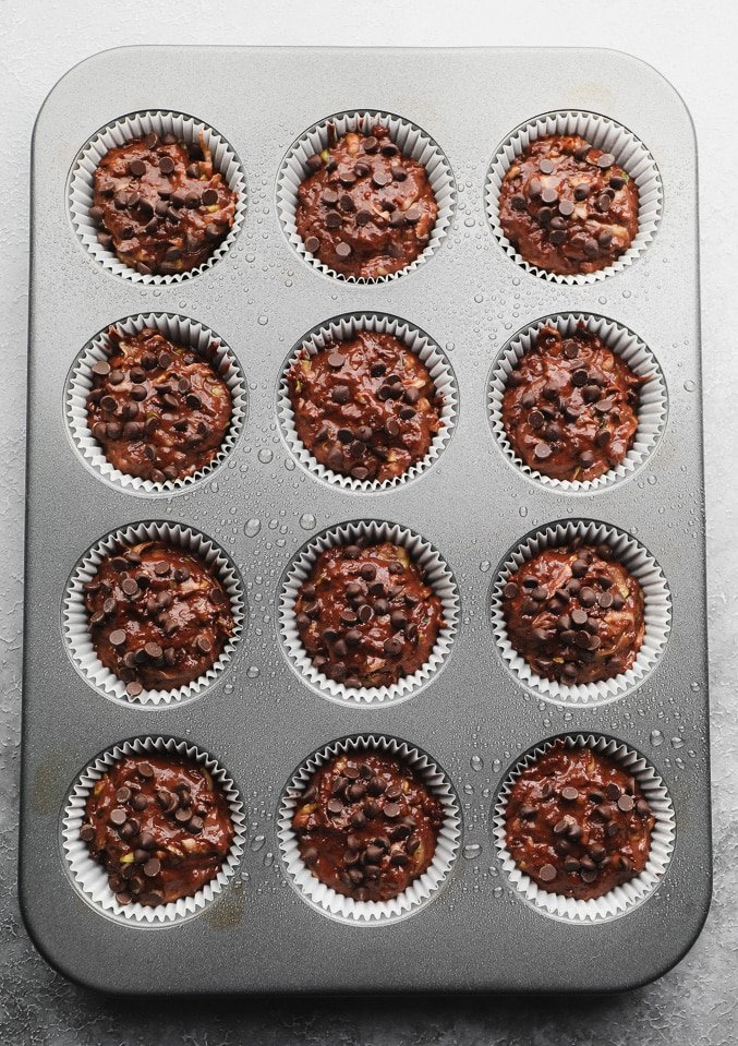 unbaked chocolate batter in a lined muffin tin