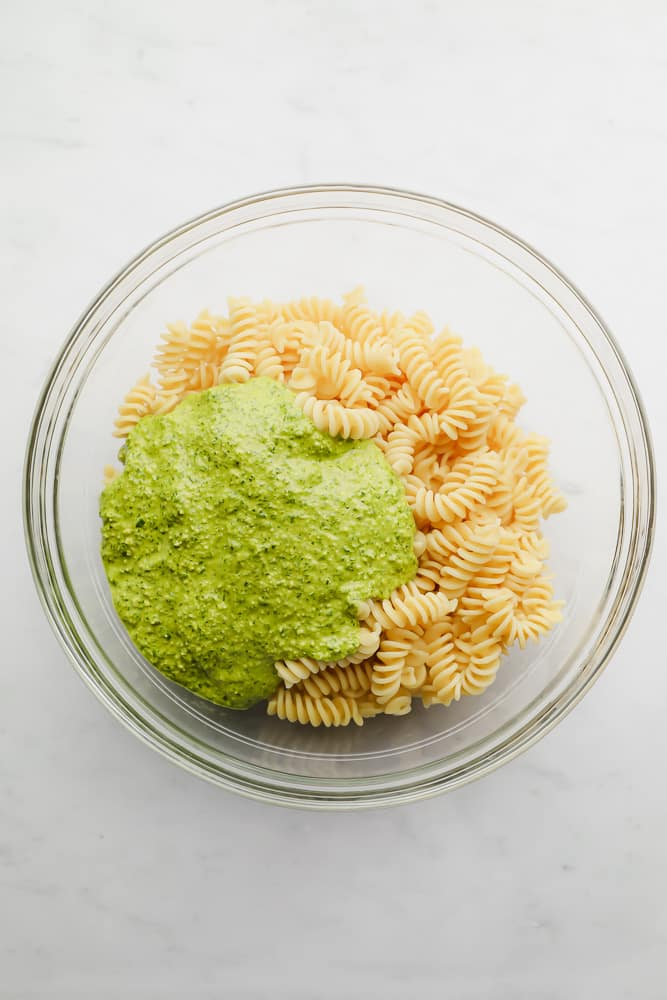pesto poured on top of cooked pasta in a glass bowl