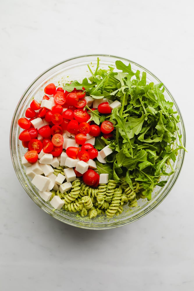 glass bowl filled with pesto pasta, arugula, cherry tomatoes, and cubed vegan cheese