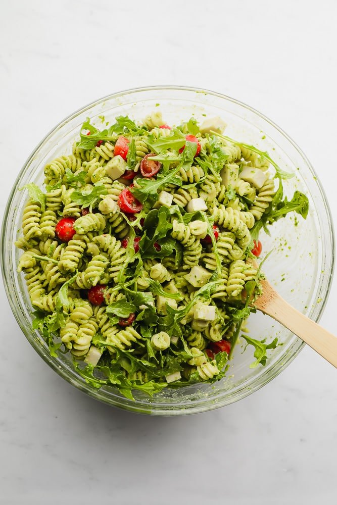 wooden spoon mixing a green pasta salad in a glass bowl