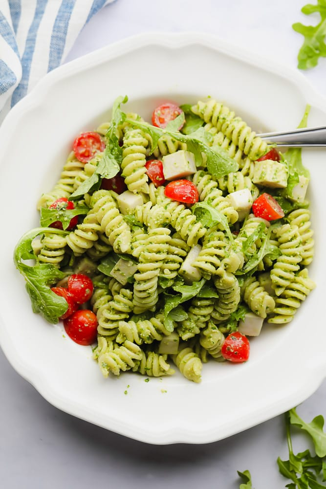 pesto pasta salad with tomatoes in a white bowl