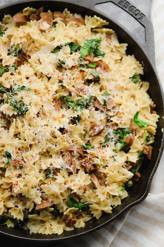 close up of vegan sausage pasta in black pan