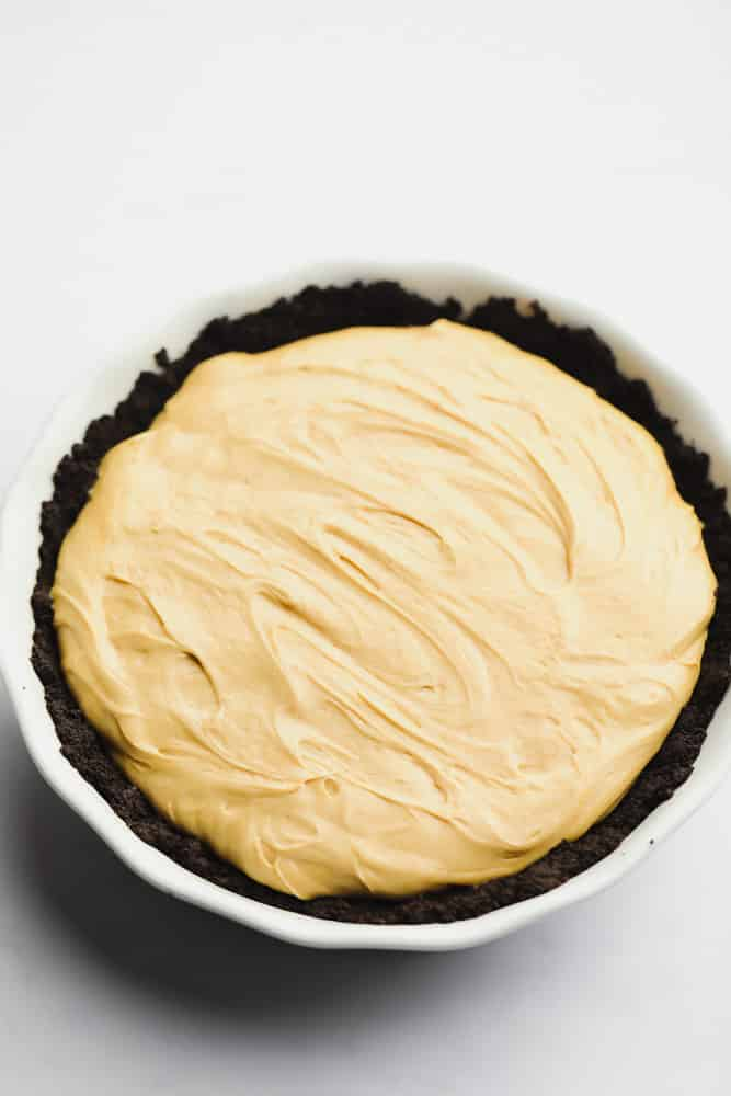 whole pie that looks creamy and brown in a oreo crust