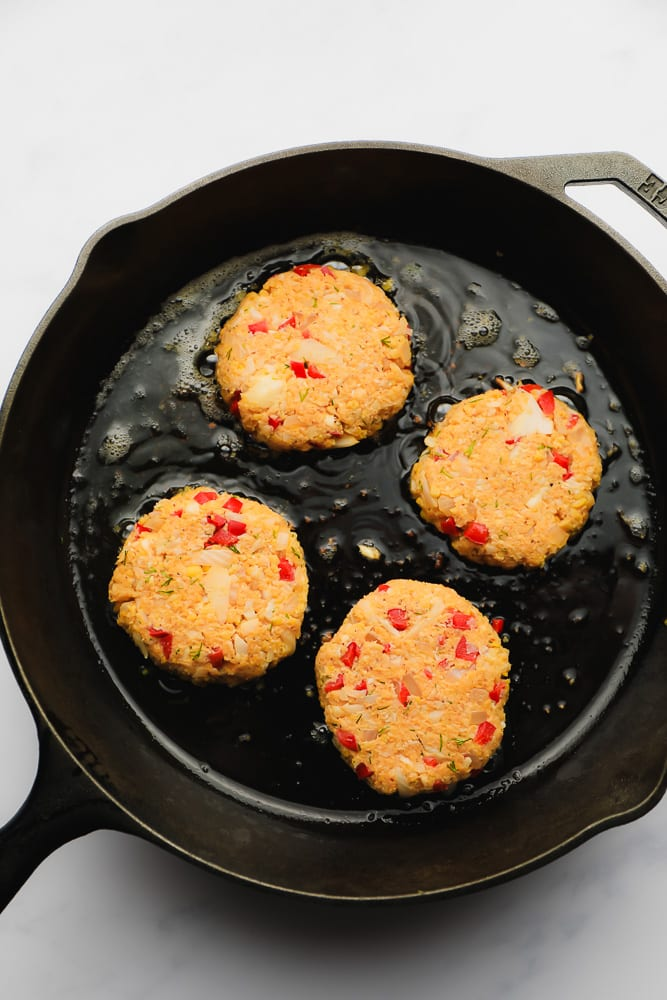 vegan crab cakes frying in a cast iron skillet
