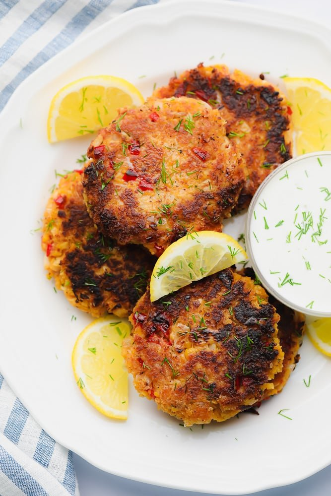 white plate with fried vegan crab cakes next to white dipping sauce and lemon wedges