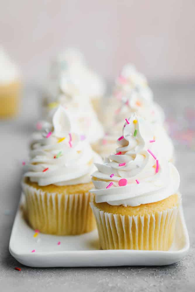several cupcakes on a white tray with sprinkles and white frosting