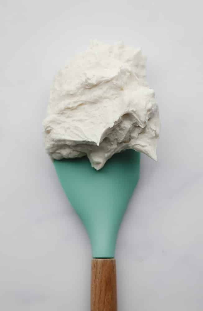 spatula with frosting on it, teal colored and white backdrop