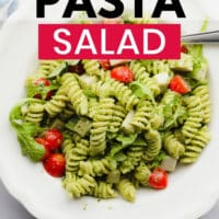 pinterest image of pesto pasta salad with tomatoes in a white bowl