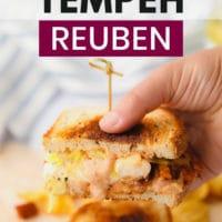 pinterest image of a woman's hand lifting 1 half of a vegan reuben sandwich