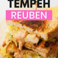 pinterest image of a vegan reuben sandwich sliced in half with sauerkraut and russian dressing leaking out