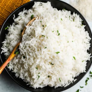 wooden spoon taking a scoop of white rice out of a black bowl