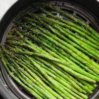 close up of cooked asparagus in an air fryer basket