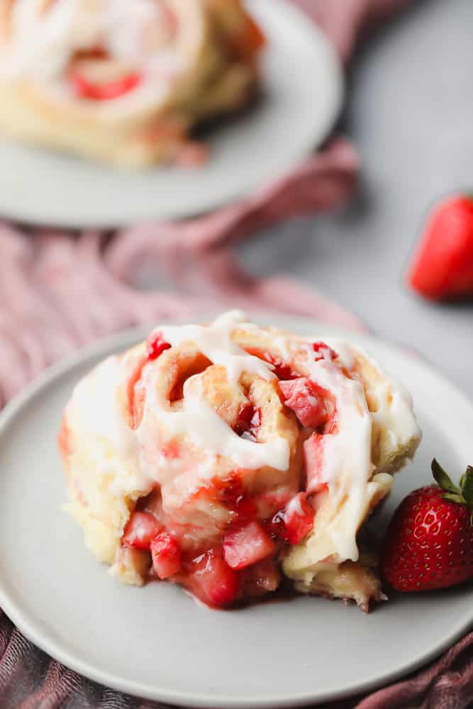 one roll on a grey plate with icing and strawberries
