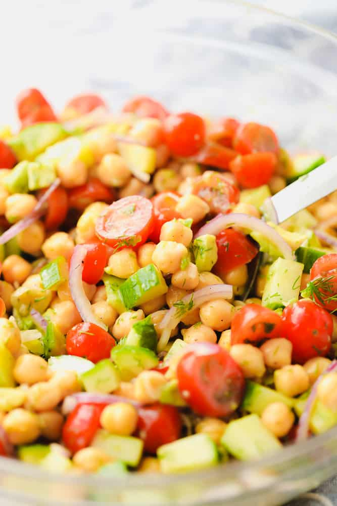 close up on a chickpea salad in a glass bowl with tomatoes, cucumber, and onion