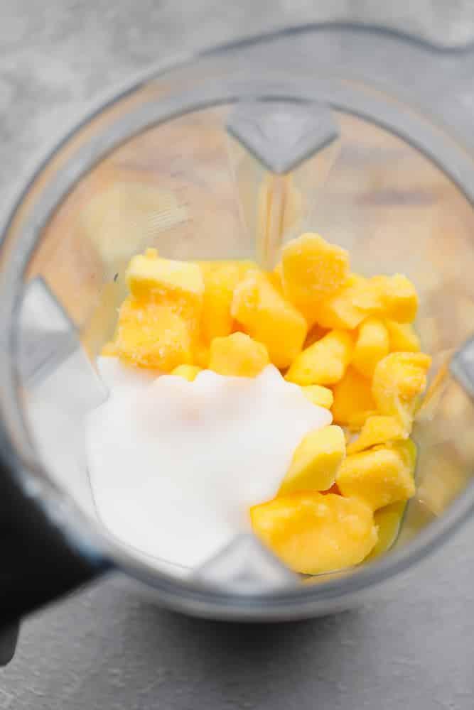 yellow mango chunks and white coconut yogurt in a blender